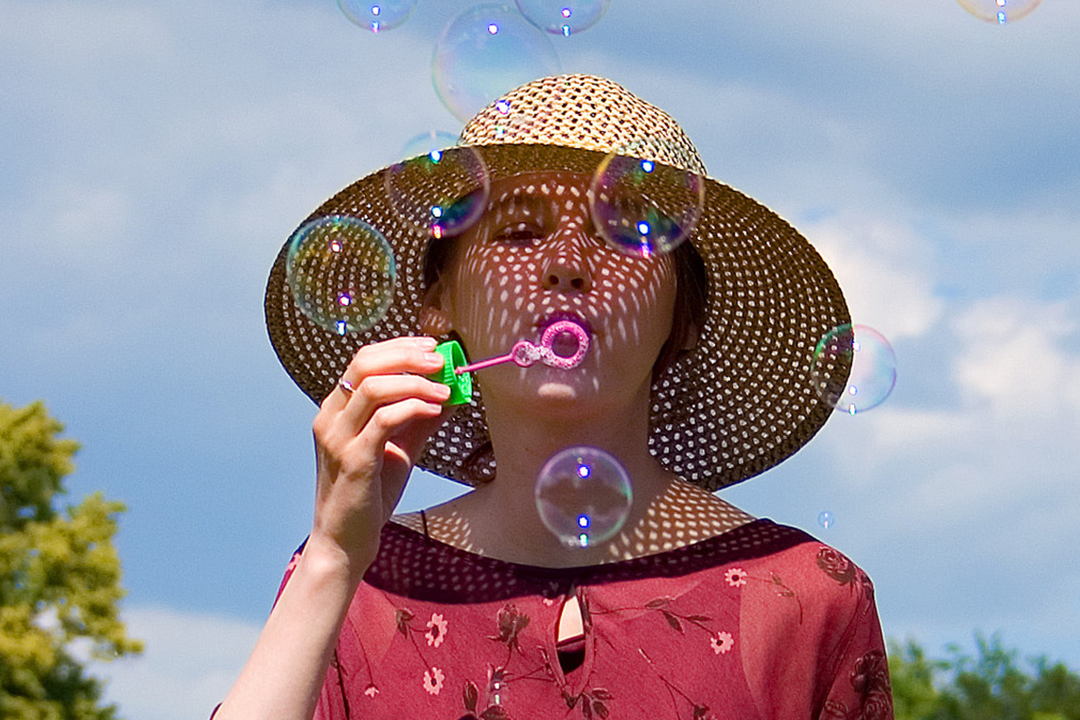 Adult woman in sun hat blowing bubbles