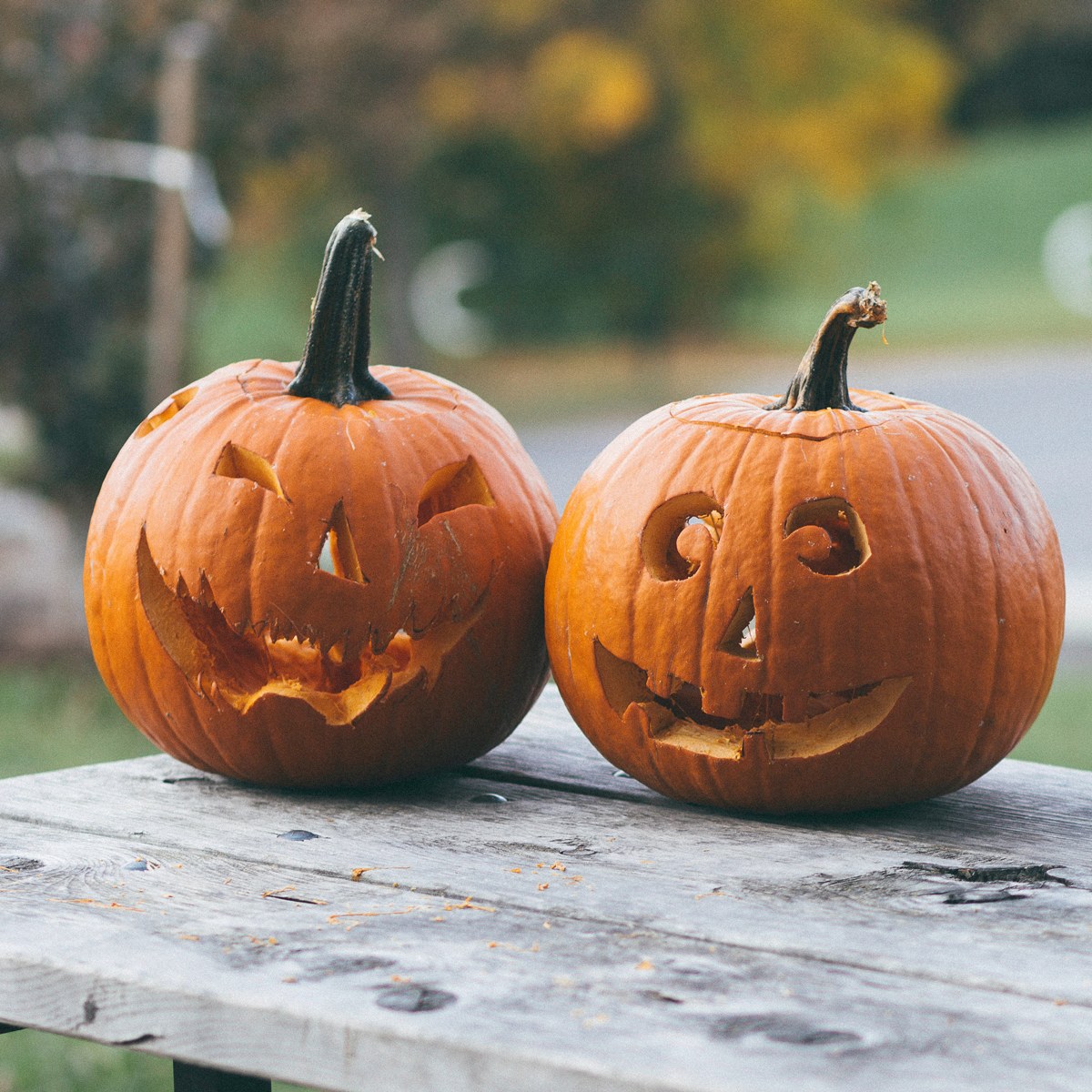 Two Halloween pumpkins with carved faces sitting on a wooden table outside